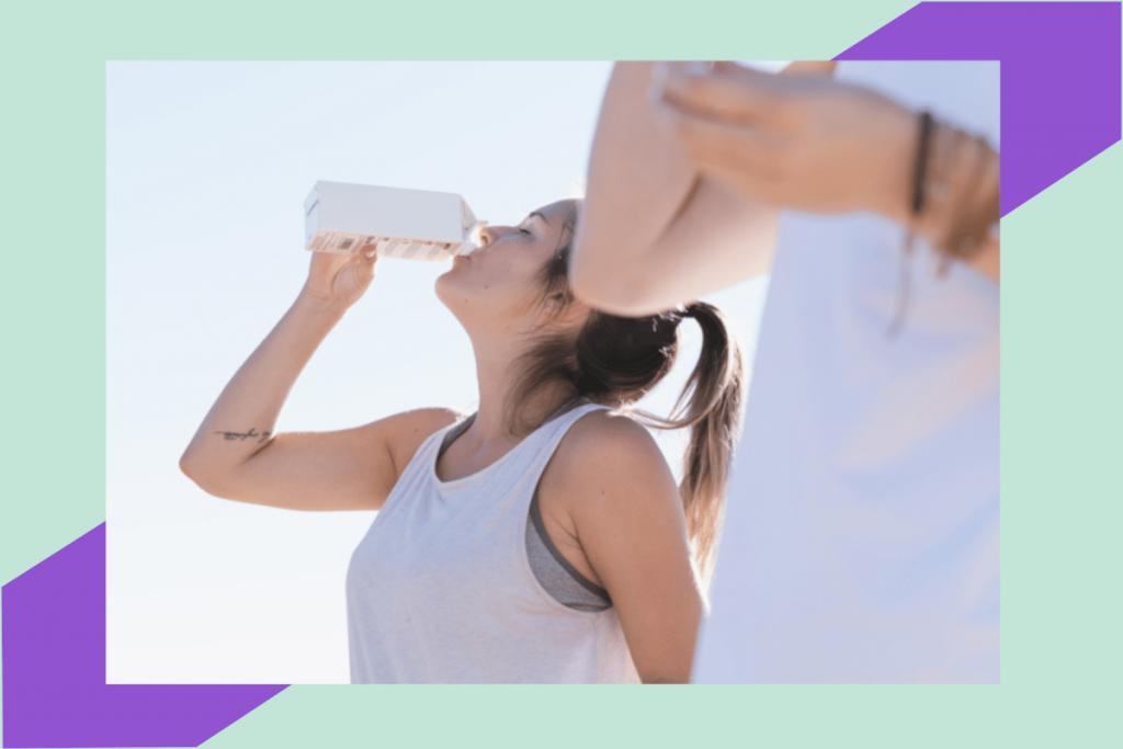 zena pije vodu dok vjezba